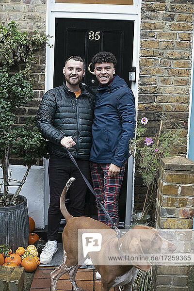 Porträt glücklich Homosexuell männliches Paar mit Hund auf vorderen stoop