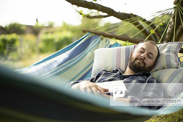 Serene Mann mit digitalen Tablette schlafen im Hinterhof Sommer Hängematte