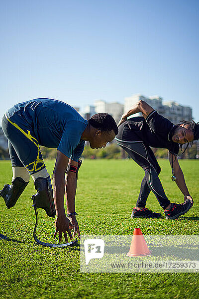 Trainer und junger männlicher amputierter Sportler beim Stretching im sonnigen Park