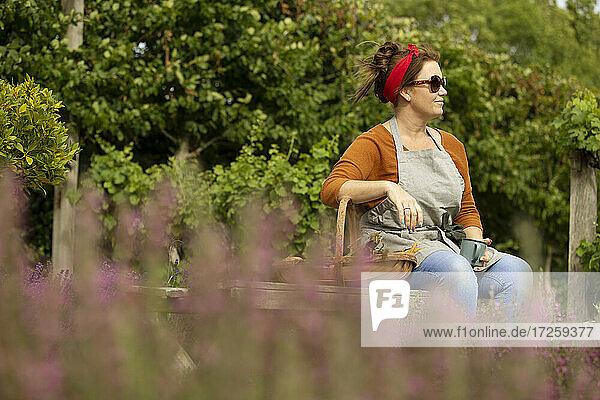 Frau mit Sonnenbrille nimmt eine Pause von der Gartenarbeit im Sommer Hinterhof