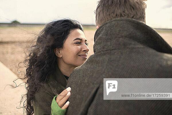 Happy woman hugging boyfriend on beach