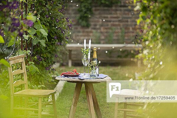 Champagner und rote Johannisbeeren auf idyllischem Gartentisch mit Kerzen