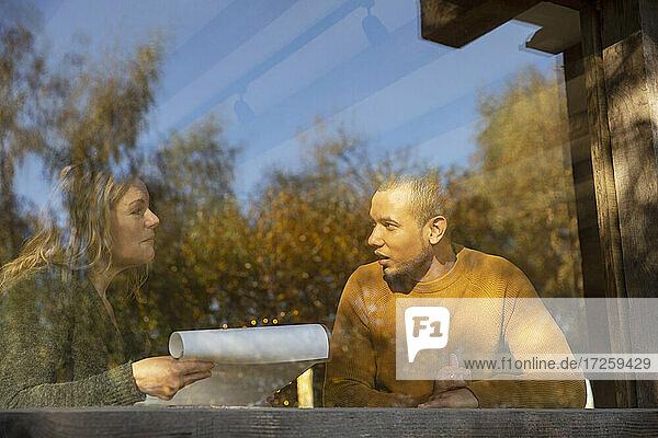 Geschäftsleute diskutieren Papierkram an sonnigen Café Fenster