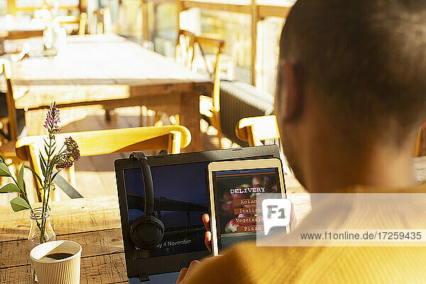 Male restaurant owner reviewing online delivery on digital tablet