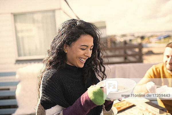 Glückliche Frau genießt Eintopf auf sonniger Terrasse
