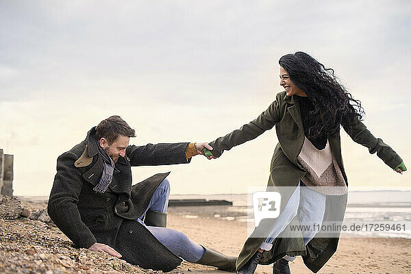 Playful couple in winter coats on beach