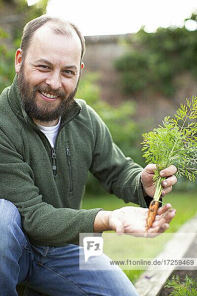 Porträt glücklicher Mann mit Bart zeigt frisch geerntete Karotte im Garten