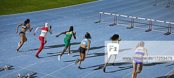 Leichtathletinnen rennen im Wettbewerb auf Hürden zu