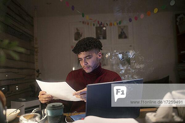 Konzentrierter junger Mann mit Papierkram arbeitet spät im Home Office