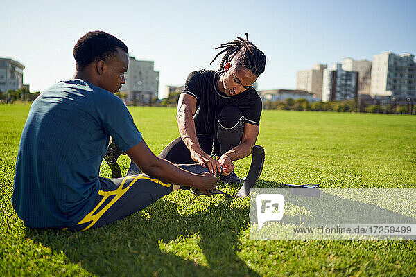 Coach helping young male amputee athlete with running blade prosthetic