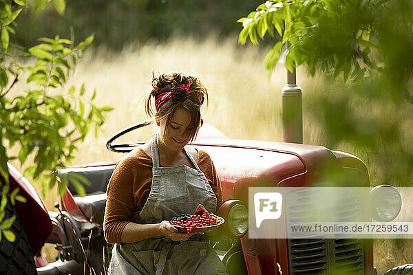 Happy woman with fresh harvested red currants at tractor