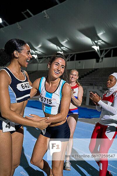 Glückliche Leichtathletik-Staffelläuferinnen beim Feiern auf der Bahn
