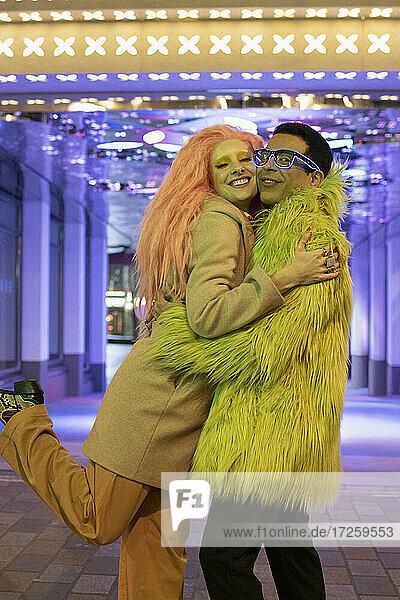 Portrait happy stylish couple hugging under neon lights on sidewalk
