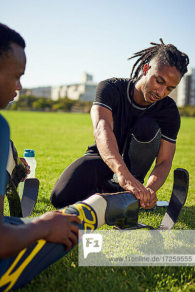 Coach helping young male amputee athlete with prosthetic in park