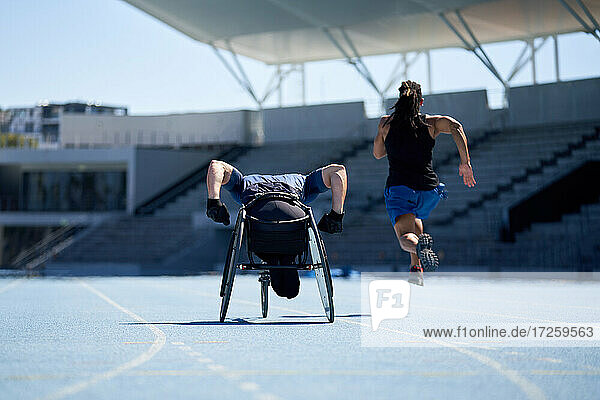 Rollstuhlsportler trainiert auf sonniger blauer Sportbahn