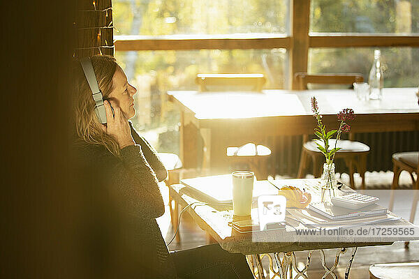 Businesswoman with headphones working in sunny cafe