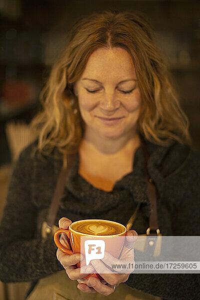 Happy female barista holding cappuccino with heart shape foam