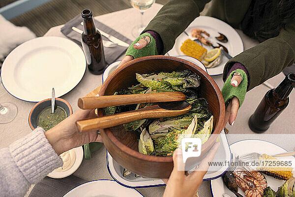 Freunde reichen Salat über Terrassentisch