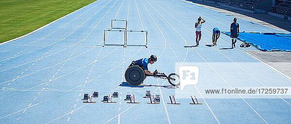 Rollstuhlsportler bereitet sich auf sonniger blauer Sportbahn vor