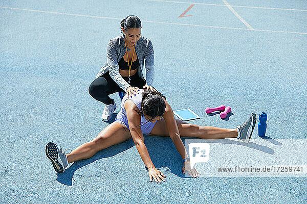 Trainer hilft weiblichen Leichtathleten beim Dehnen