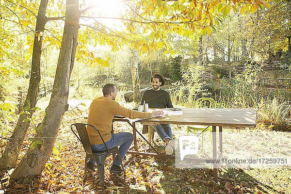 Geschäftsleute treffen sich am Tisch im sonnigen idyllischen Herbstpark