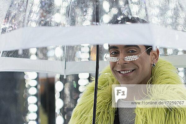 Porträt stilvoller junger Mann in Federboa unter Regenschirm
