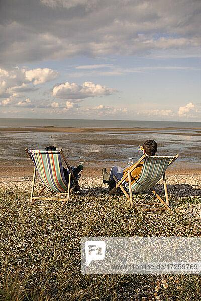 Paar entspannt mit Wein in Strandstühlen am sonnigen Meer