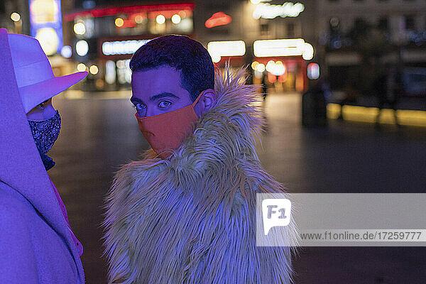 Porträt modischen jungen Mann in Gesichtsmaske auf Stadt Straße in der Nacht