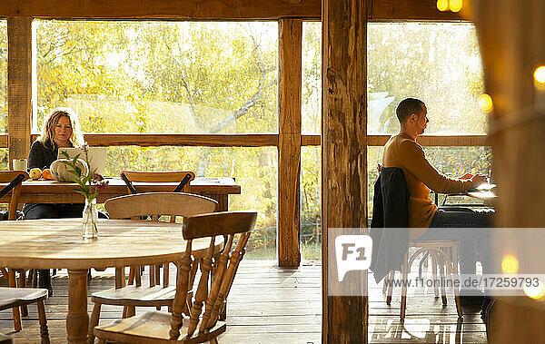 Geschäftsleute arbeiten im sonnigen Herbst Cafe