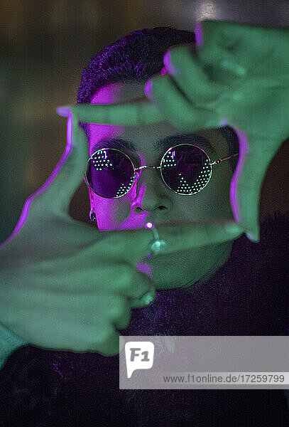 Portrait cool young man in sunglasses forming finger frame in neon
