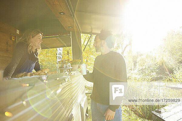 Food truck owner and customer talking in sunny autumn park