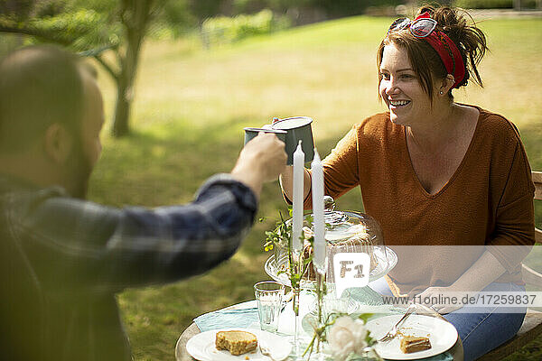 Happy couple enjoying tea and cake at table in sunny garden