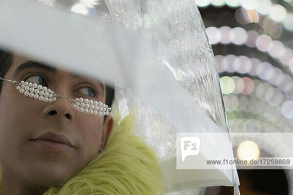 Close up stilvollen jungen Mann mit Birne Brille unter Regenschirm