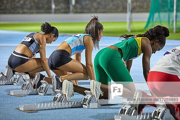 Leichtathletinnen an den Startblöcken auf der Bahn