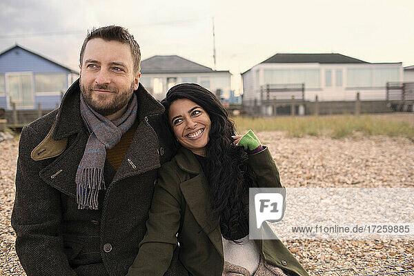 Happy couple in winter coats on beach