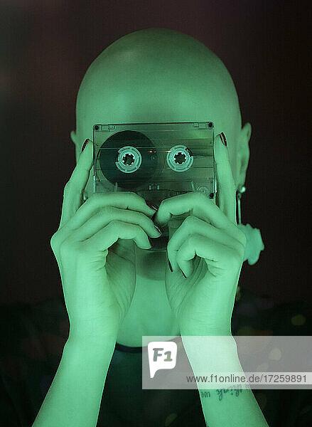 Porträt Frau mit rasiertem Kopf hält Kassettenband in grünem Licht