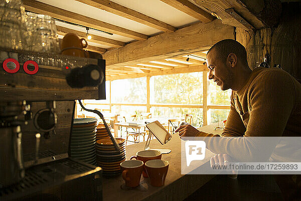Männlicher Café-Besitzer mit digitalem Tablet hinter der Theke