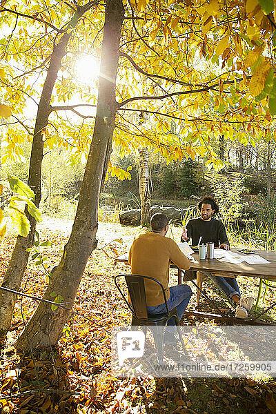 Geschäftsleute Treffen am Tisch in sonnigen Herbst Park