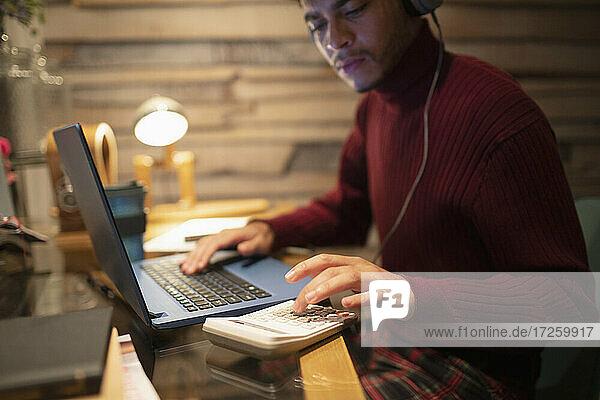 Junger Mann mit Kopfhörer mit Taschenrechner am Laptop im Home-Office