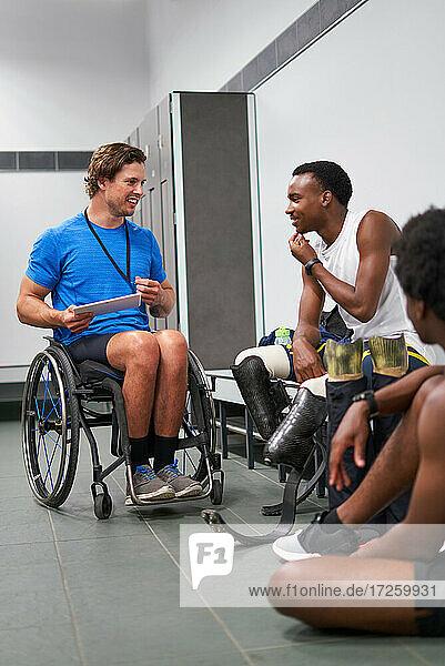 Rollstuhl- und amputierte Sportler mit digitalem Tablet in der Umkleidekabine