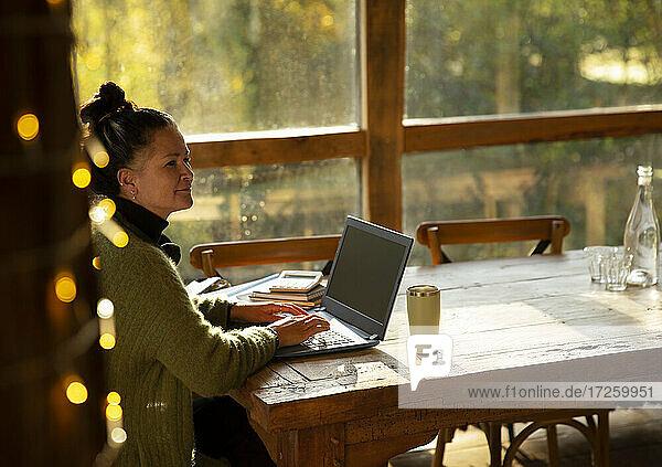 Nachdenkliche Geschäftsfrau arbeitet am Laptop im Café
