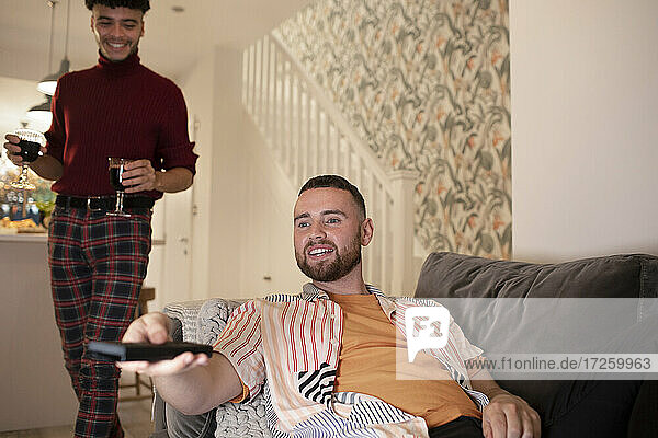 Gay male couple with wine watching TV at home