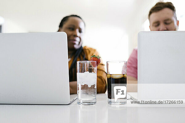 Wasser und Limonade in Gläsern zwischen Mann und Frau  die an Laptops arbeiten
