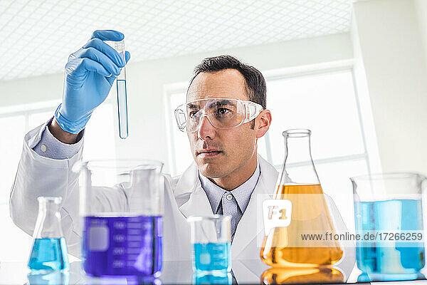 Wissenschaftlerin betrachtet blaue Flüssigkeit im Labor