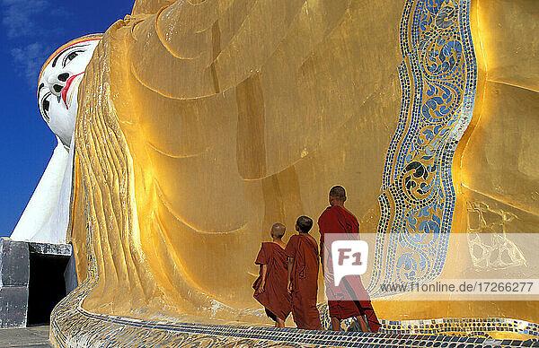 Myanmar  Monyma  Mandalay Division  Novizenmönche beten unter der riesigen Statue des liegenden Buddhas im Lay Kyune Sakkyar Tempel
