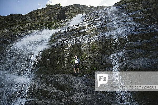 Russland  Karatschai-Tscherkessien  Arkhyz  Mann stehend in der Nähe von Sofiyskiye Vodopady Wasserfall im Kaukasus-Gebirge
