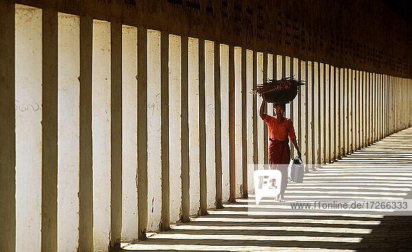 Myanmar  Bagan  Mandalay Division  Frau geht im Säulengang der Schwezigon-Pagode und trägt Holz auf dem Kopf