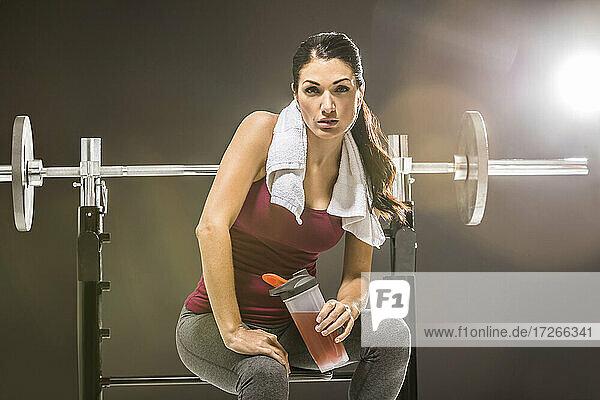 Studio-Porträt einer Frau in ärmellosem Oberteil  die an einer Langhantel sitzt