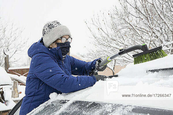 USA  New Mexico  Santa Fe  Frau mit Gesichtsmaske entfernt Schnee vom Auto