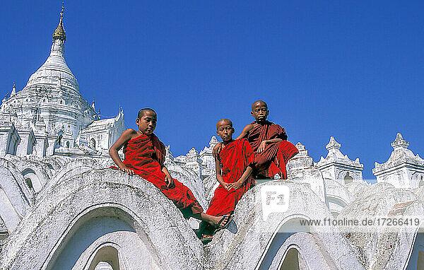 Myanmar  Mingun  Mandalay Division  Buddhistische Mönche sitzen auf den weißen Bögen der Hsinbyume-Pagode